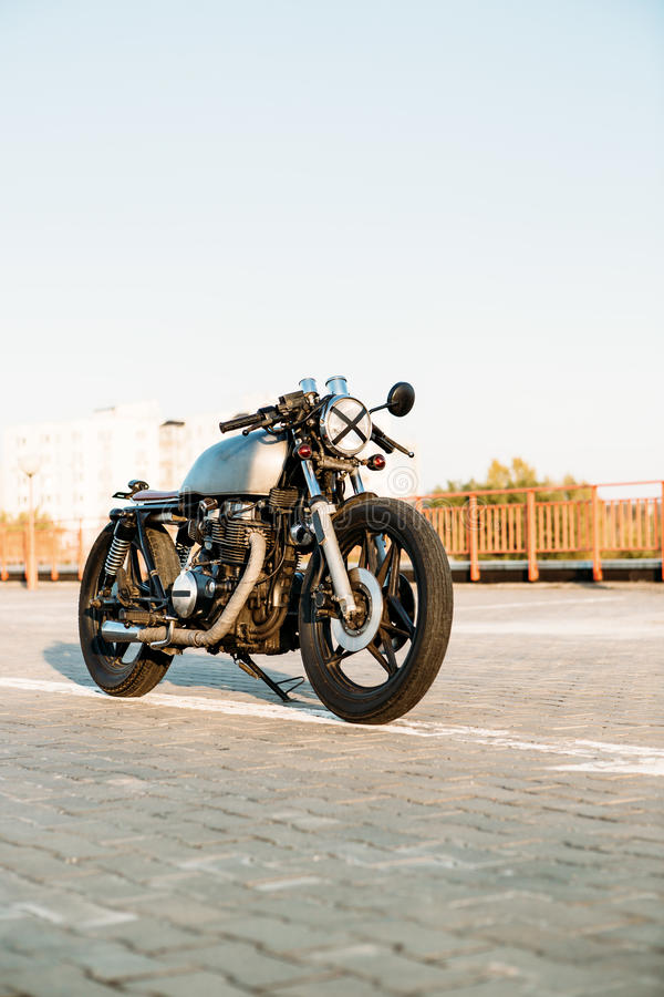 Silver vintage custom motorcycle caferacer. Front view of silver vintage custom motorbike motorcycle caferacer on empty rooftop parking lot surrounded by urban royalty free stock photo