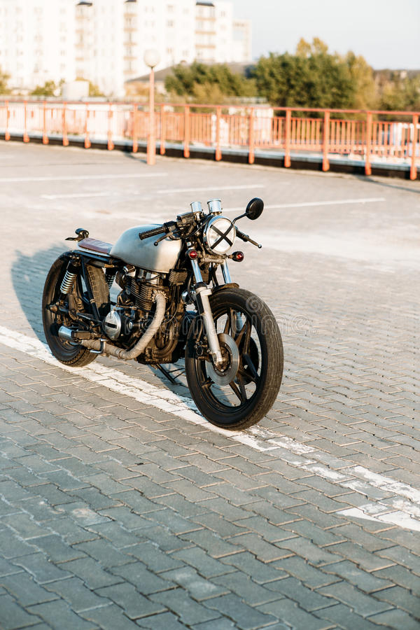 Silver vintage custom motorcycle caferacer. Front view of silver vintage custom motorbike motorcycle caferacer on empty rooftop parking lot surrounded by urban royalty free stock images