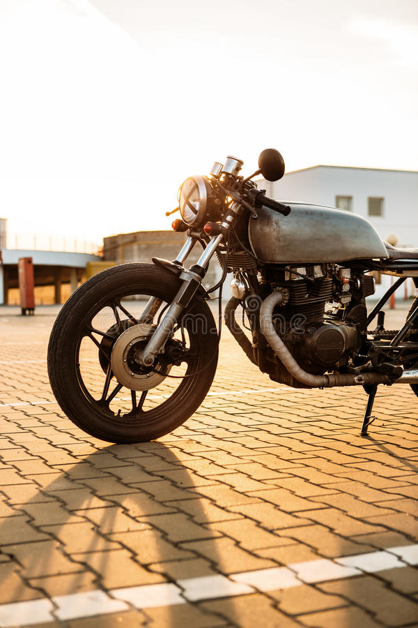 Silver vintage custom motorcycle caferacer. One silver vintage custom motorcycle cafe racer motorbike on empty rooftop parking lot surrounded by urban stock photography