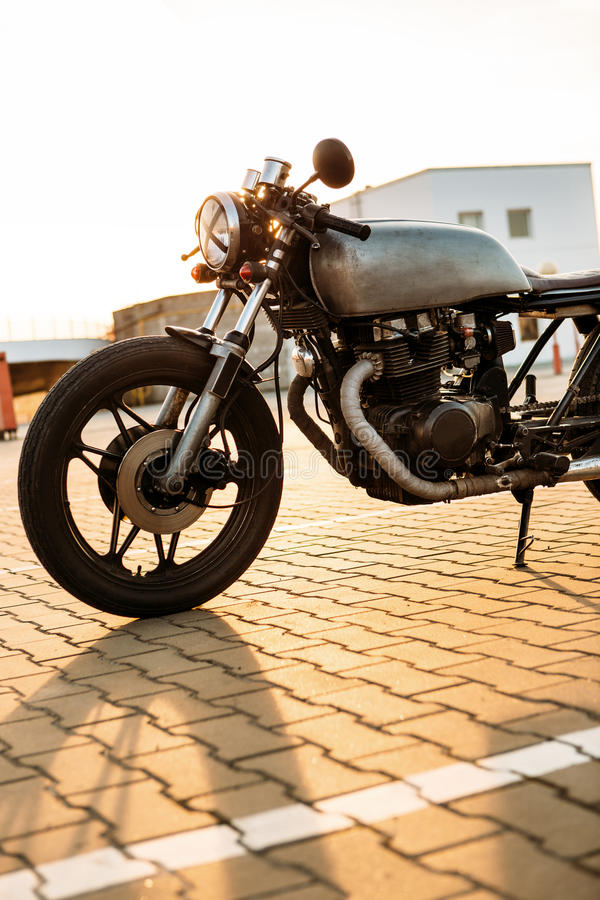 Silver vintage custom motorcycle caferacer. One silver vintage custom motorbike cafe racer motorcycle at empty rooftop parking lot surrounded by urban stock photography