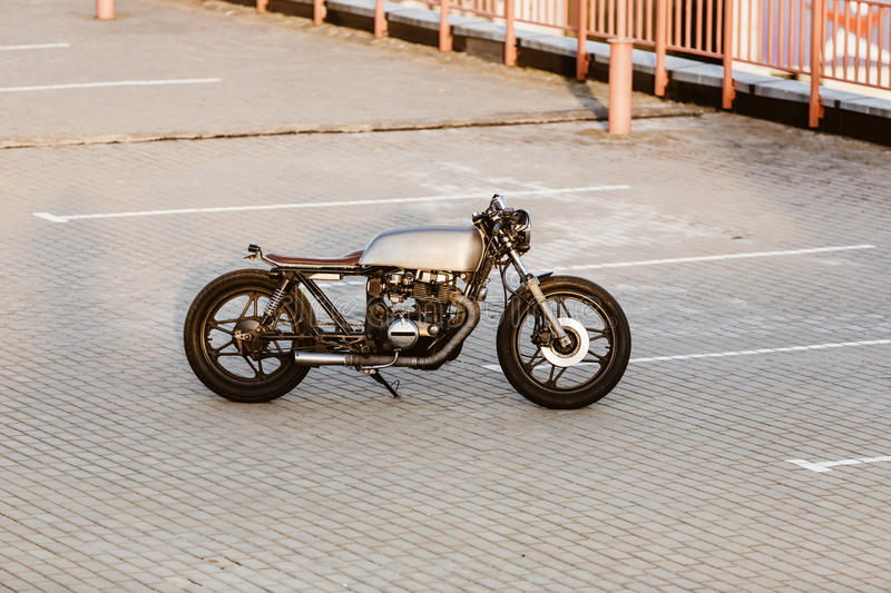 Silver vintage custom motorcycle caferacer. One silver vintage custom motorbike caferacer motorcycle on empty rooftop parking lot at city center surrounded by royalty free stock photography
