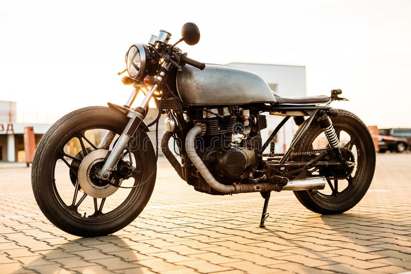 Silver vintage custom motorcycle caferacer. One silver vintage custom motorbike caferacer motorcycle on empty rooftop parking lot surrounded by urban royalty free stock photo