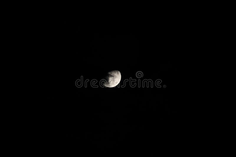 Silver waxing gibbon moon in a starless sky. Sliver of a silver waxing gibbon moon at a distance behind clouds surrounded by the dark abyss of night as seen from royalty free stock images