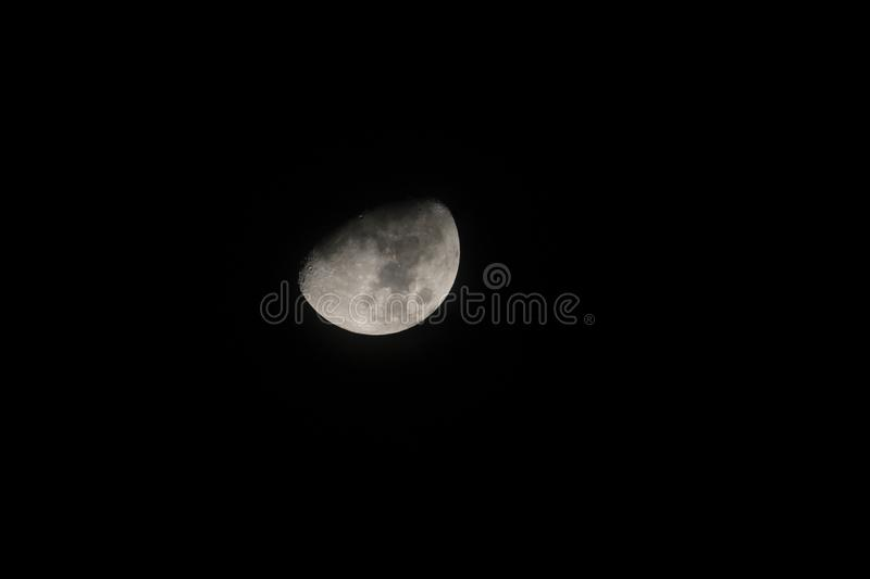 Silver waxing gibbon moon in a starless sky. Sliver of a silver waxing gibbon moon surrounded by the dark abyss of night as seen from earth royalty free stock photography