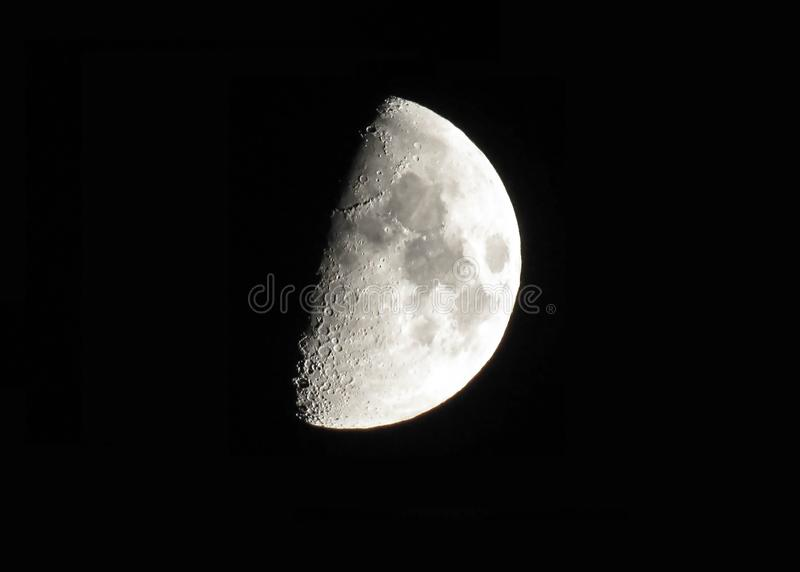 Silver waxing moon on black sky background stock photo