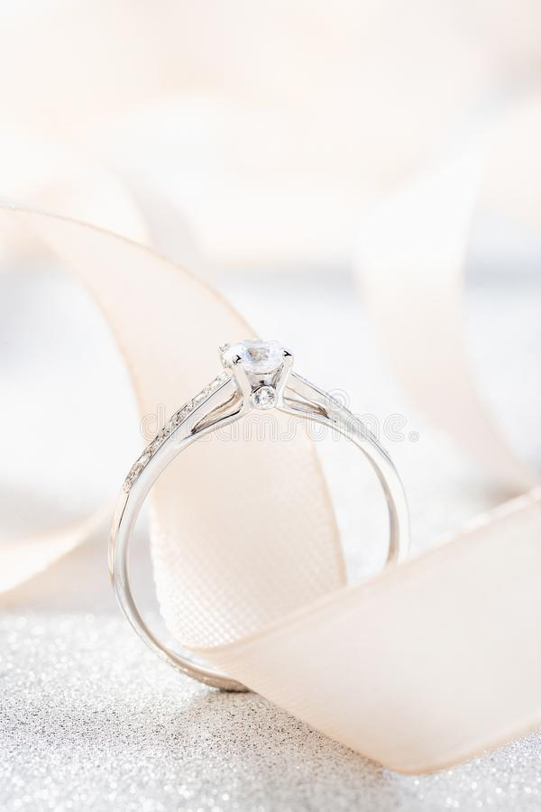Silver wedding diamond ring on white sparkle background with beige ribbon. White gold engagement or proposal ring with gemstones royalty free stock photography