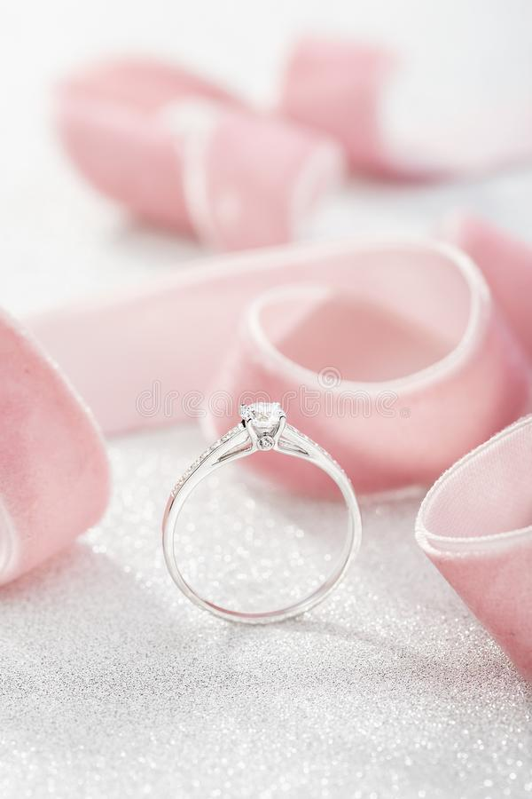 Silver wedding diamond ring on white sparkle background with pink ribbon. White gold engagement or proposal ring with gemstones stock images