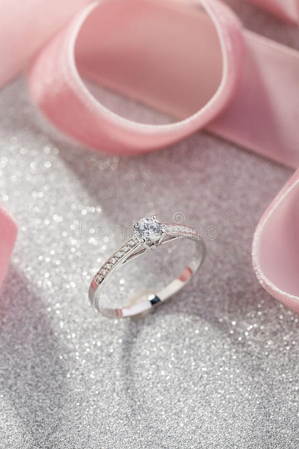 Silver wedding diamond ring on white sparkle background with pink ribbon. White gold engagement or proposal ring with gemstones royalty free stock photos