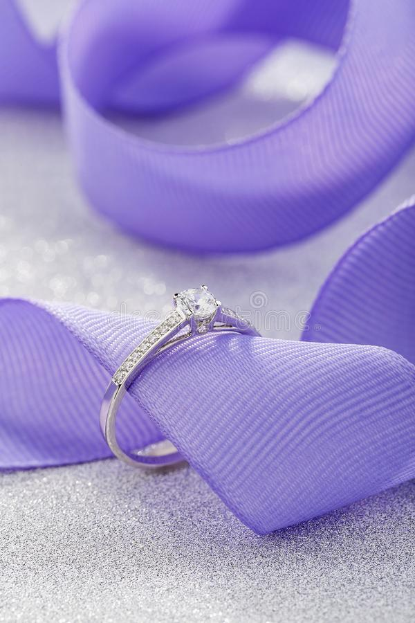 Silver wedding diamond ring on white sparkle background with purple ribbon. White gold engagement or proposal ring with gemstones royalty free stock photography