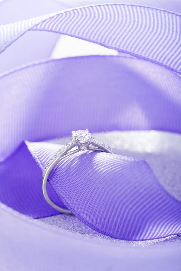 Silver wedding diamond ring on white sparkle background with purple ribbon. Silver wedding diamond ring on white sparkle background with violet ribbon. White stock images