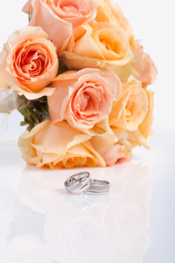 Silver wedding rings and a bridal bouquet stock image