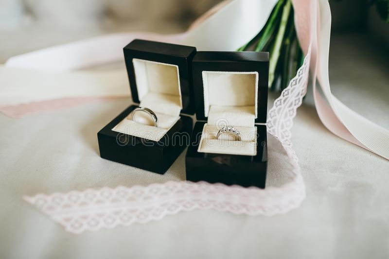 Silver wedding rings with gems in a beautiful black boxes on the piece of the ribbon. Close-up. Artwork royalty free stock photography