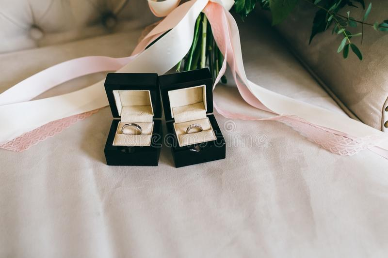 Silver wedding rings with gems in a beautiful black boxes on the piece of the ribbon. Close-up. Artwork royalty free stock image
