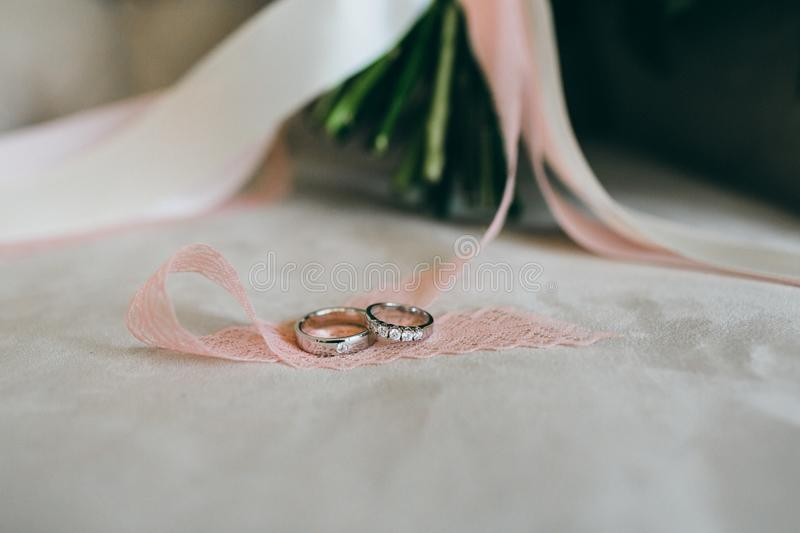 Silver wedding rings with gems on the piece of the ribbon. Close-up. Artwork stock images
