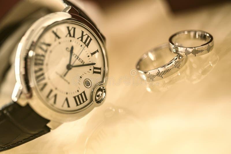 Silver Wedding Rings Near Silver Round Analog Watch stock photos