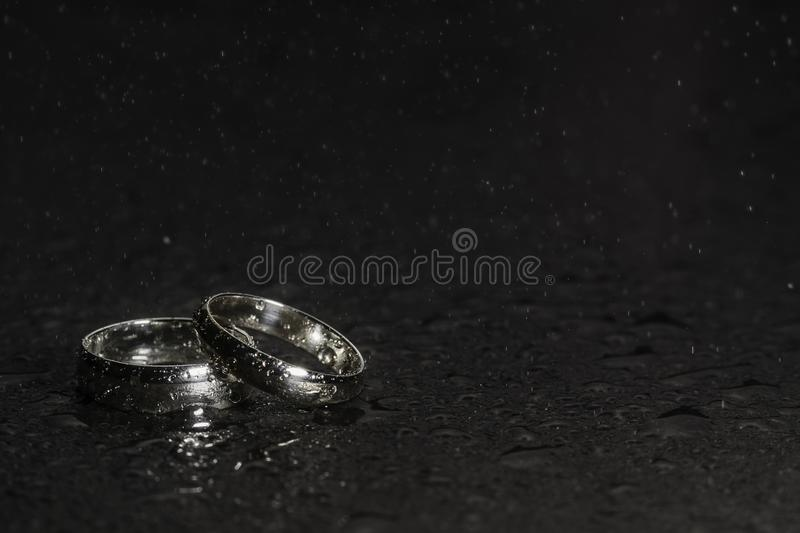 Silver Wedding Rings on a rock background with water droplets and spray. In the air stock photography
