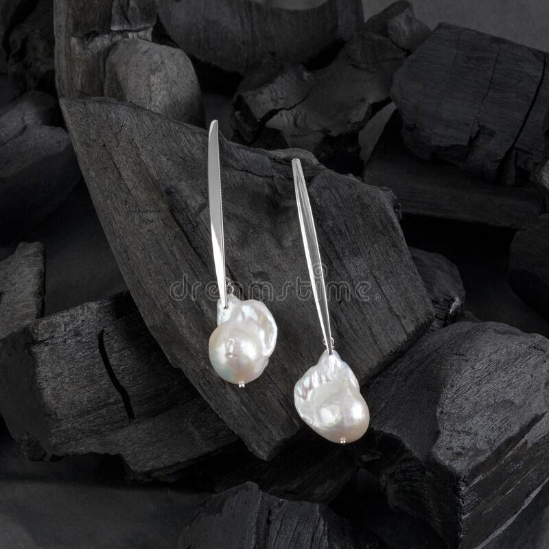 Silver white baroque pearl earrings stock photography