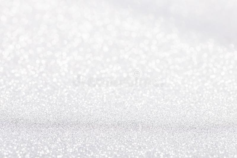 Silver white sparkle bokeh background. Abstract defocused glitter backdrop. Copy space royalty free stock photography
