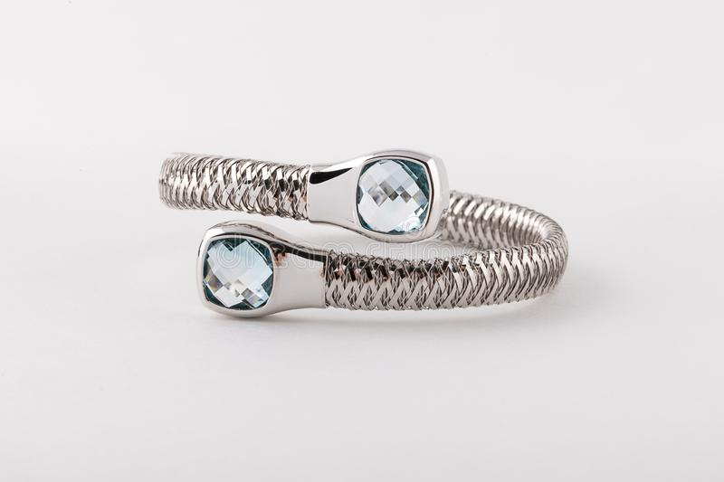 Silver womens bracelet  with two light blue diamonds in  shape of two square  on white background. royalty free stock images