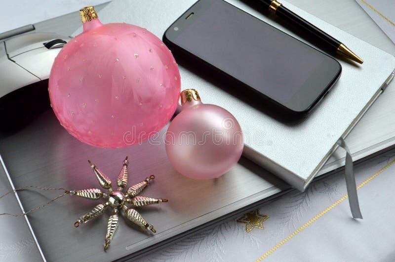Silverbärbar datordator med rosa julboll-, garnering-, androidmobiltelefon-, anteckningsbok-, penn- och kopieringsutrymme arkivbild