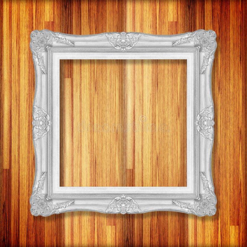 Silverbildram på träväggen; Den tomma bildramen uppvaktar på royaltyfria bilder