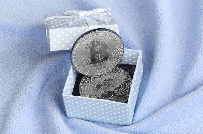Silverbitcoinlögnerna i en liten blå gåvaask med en liten pilbåge på en filt som göras av mjukt och fluffigt ljus - blåa ullbeklä royaltyfri fotografi
