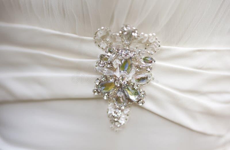 Silverbrosch med stora bergkristaller på den vita siden- klänningen arkivfoton