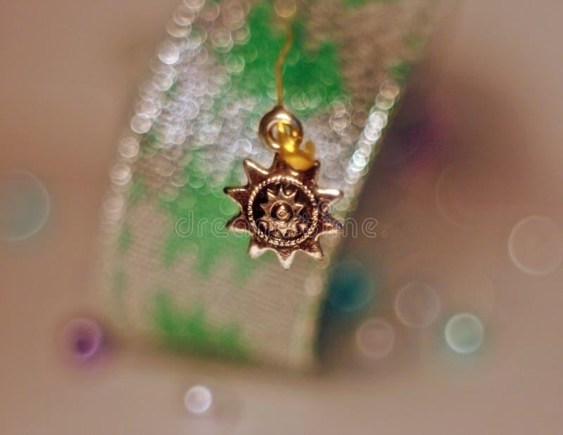 Silverhänge som klämmas fast med ett guld- stift till ett skinande band arkivbild