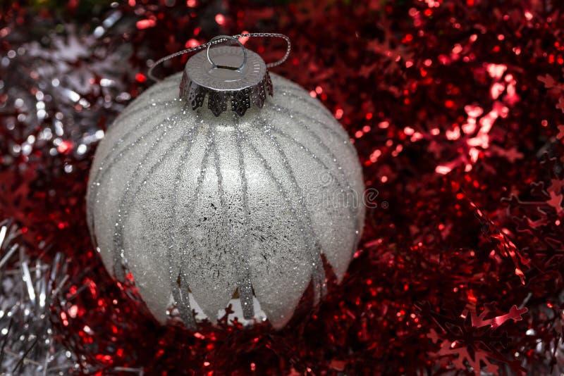 Silverjulboll på röd sparkly bakgrund royaltyfri fotografi