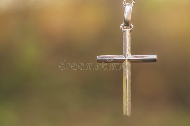 Silverkryss mot bakgrund av naturen Begreppet tro, andlighet och religion royaltyfri foto