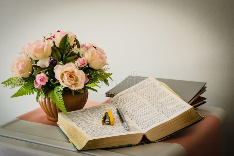 Silverpenna på boken med blomkrukan arkivbild