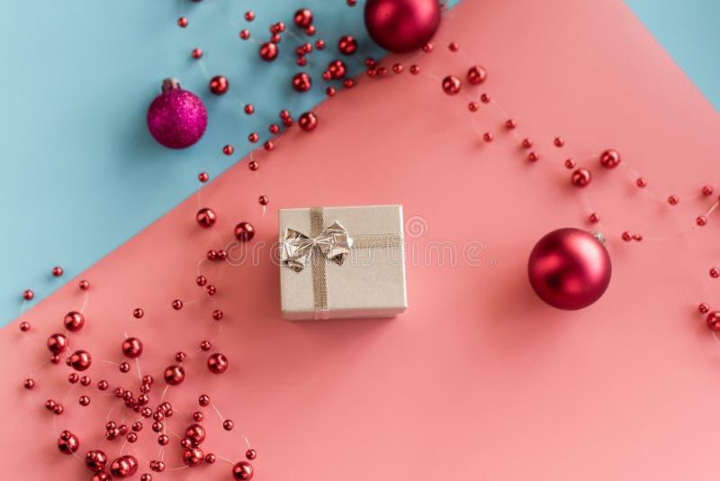 Silverpresenter på rosa och blå bakgrunder med röda julklappar och kulor Begreppet gåvor, överraskningar. arkivbild