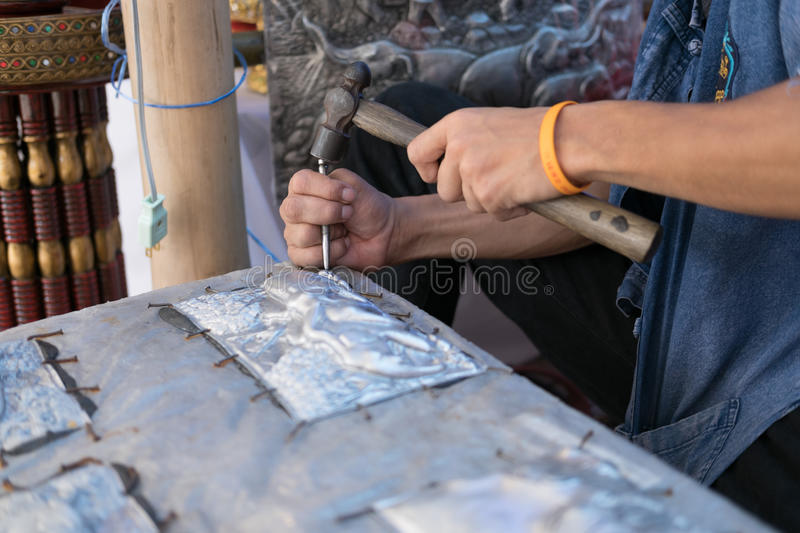 Silversmith craftsman carving elephant on a silver plate (metal stock image