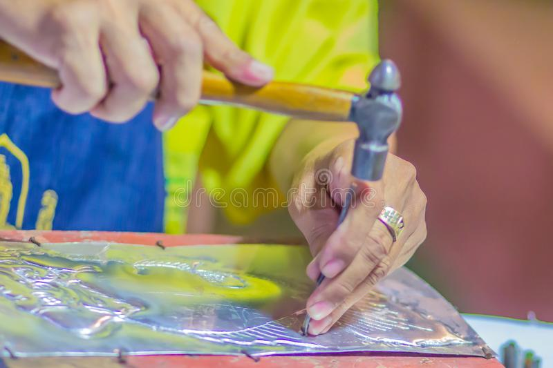 Close up Thai engraver while craving silver pattern with hammer and chisel at night. Silversmith craftsman carving pattern on a si royalty free stock photos