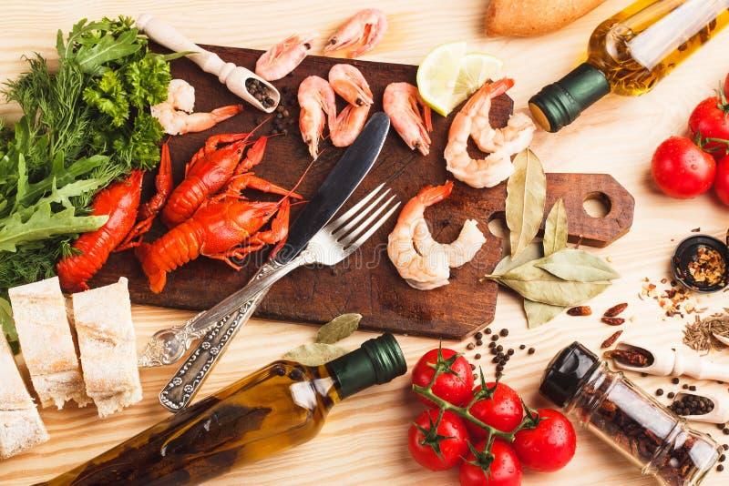 Silverware на доске с специями, томатами вишни и раками стоковое фото
