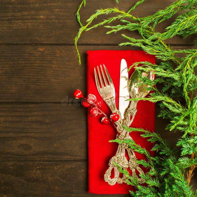Silverware рождества на красной ткани с зеленой елью стоковые фотографии rf