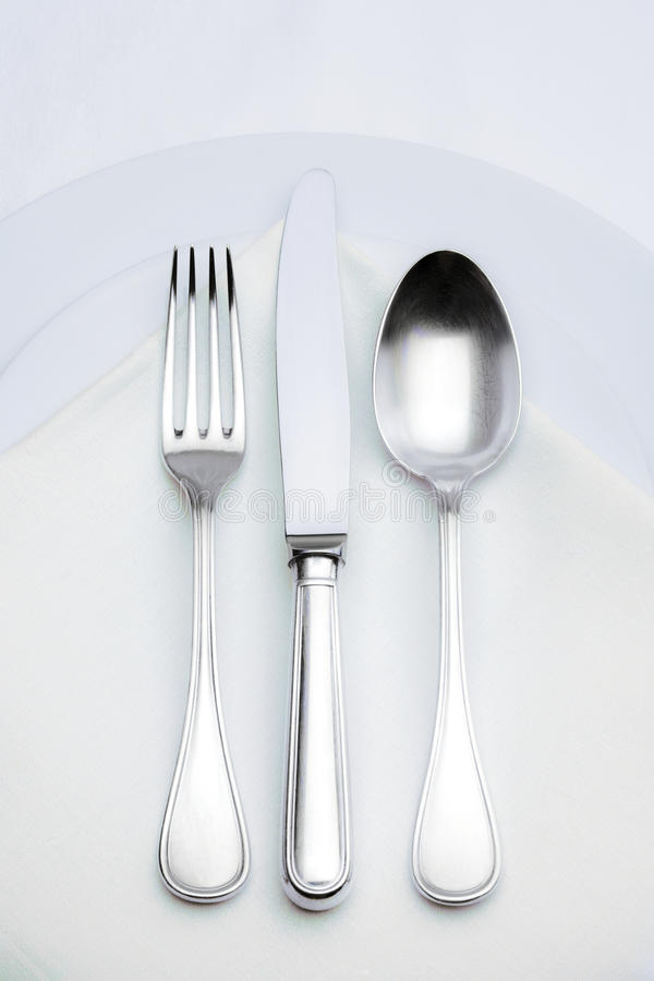 Silverware. Elegant silverware setting on plate with white cloth royalty free stock image