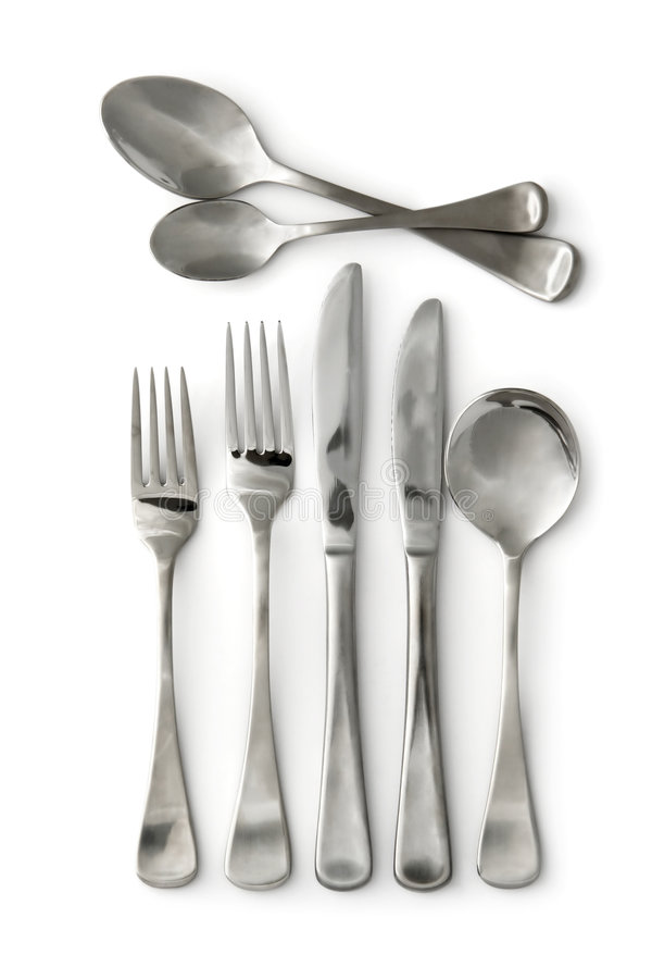 Silverware. ~ stainless steel cutlery, casting shadow on clean white background. Knives, forks, and spoons royalty free stock image