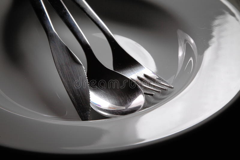 Silverware in a bowl. Simple image of silverware sitting in a white bowl royalty free stock photography