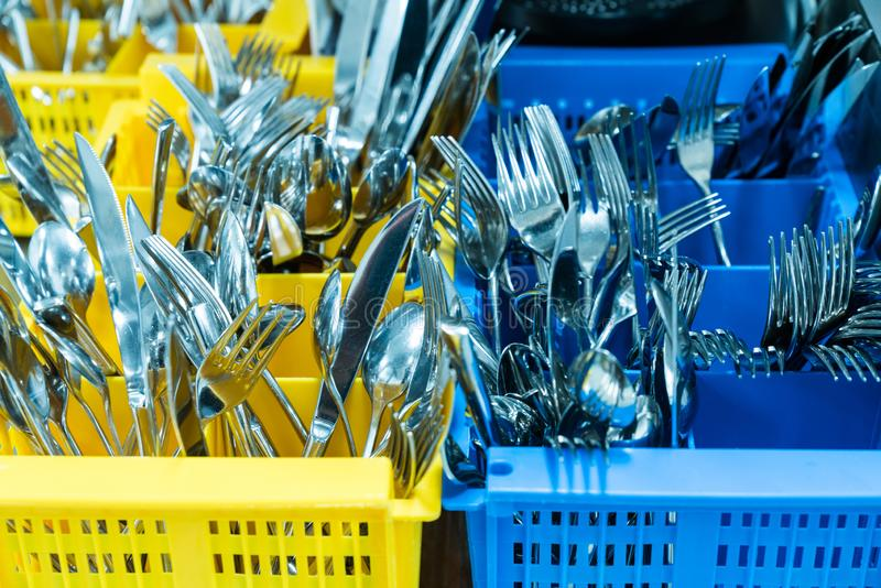 Silverware and cutlery in colorful palstic ocntainer in an industrial restaurant kitchen. Clean and fresh out of the dishwasher royalty free stock images