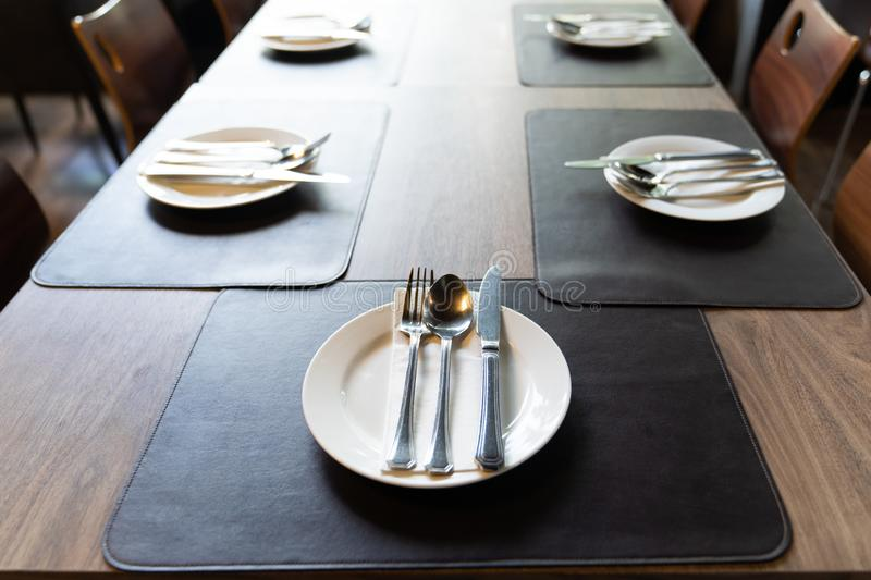Silverware with forks, knives, plates on the wood table. In restaurant served for dinner. Table setting on a big luxury table concept royalty free stock image