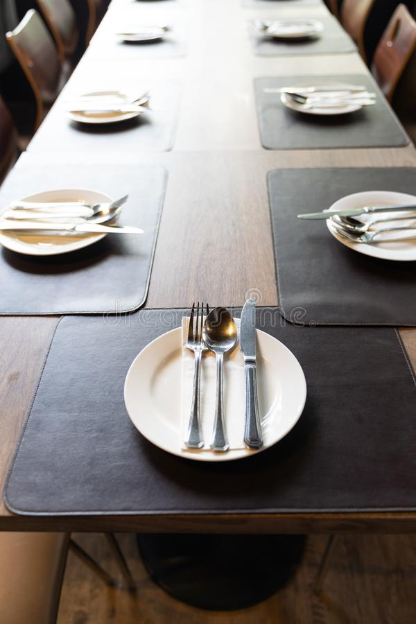 Silverware with forks, knives, plates on the wood table. In restaurant served for dinner. Table setting on a big luxury table concept stock images