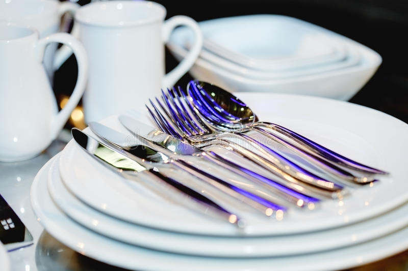 Silverware on plates. Reflecting blue light stock images