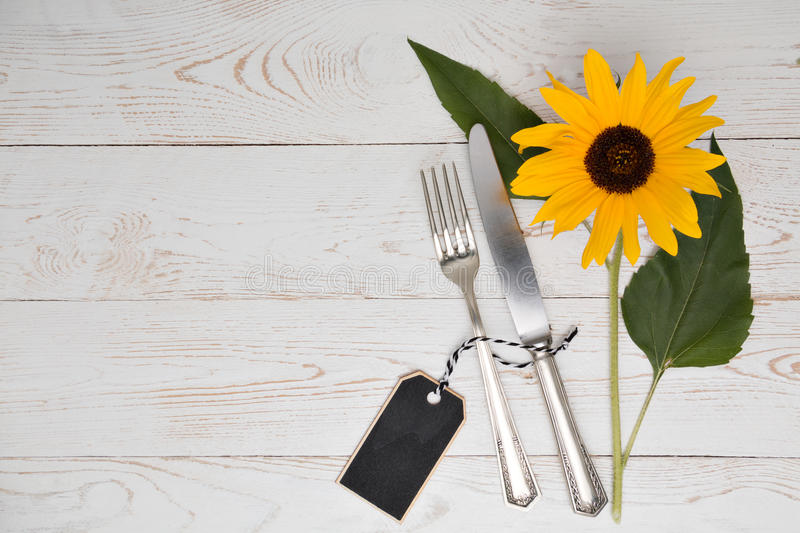Silverware with sunflower on a table. Cutlery silverware with a sunflower on an old table stock photography