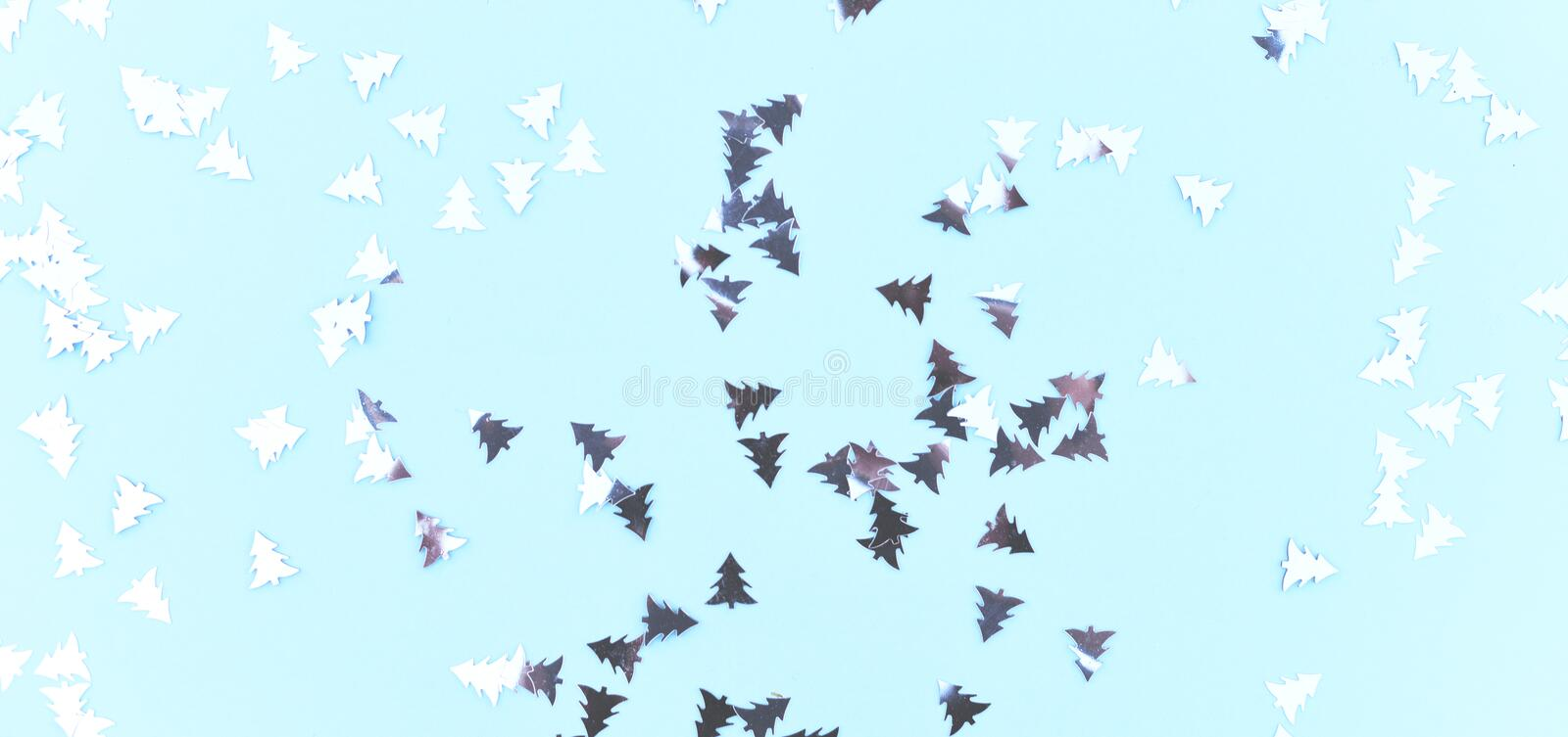 Silvery Christmas confetti on a blue background. royalty free stock photo
