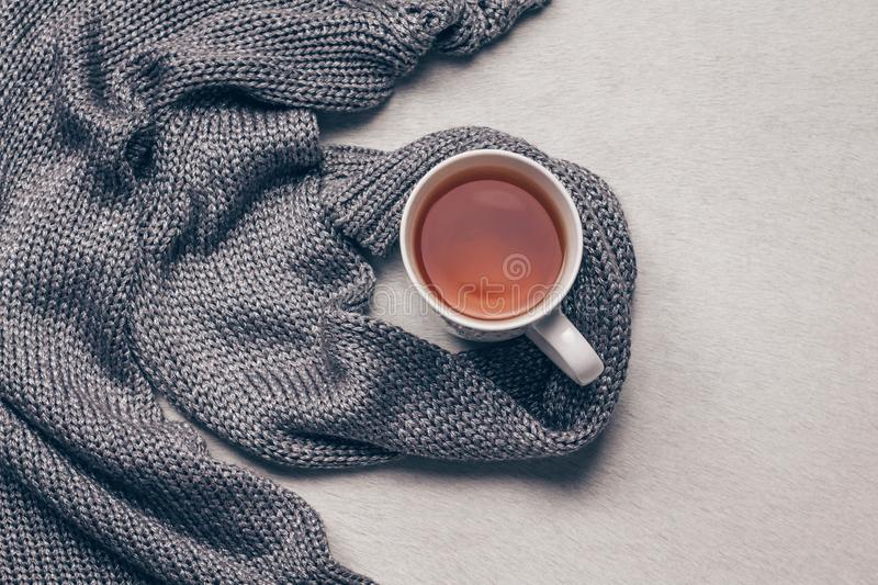 Silvery grey knitted fabric along a cup of tea on milky white fur background. Get over flu concept. Top view royalty free stock images