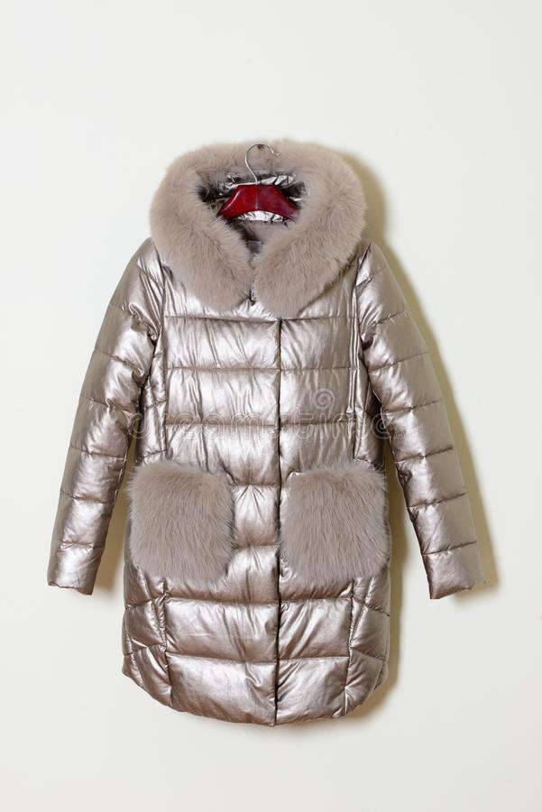 Silvery jacket with a collar on natural fur and pockets decorated with fox fur. Outerwear. Silvery jacket with a collar on natural fur and pockets decorated stock photos
