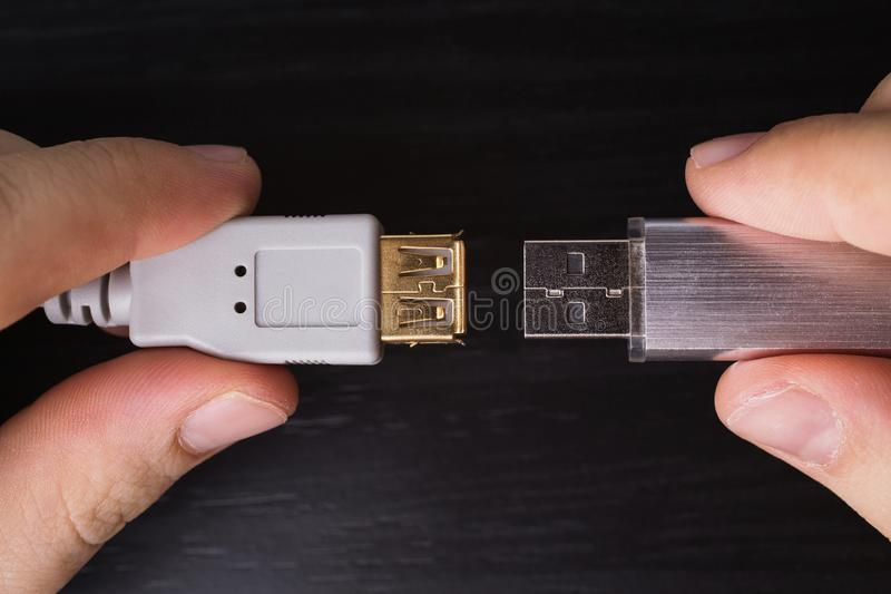 Usb flash drive connection. Silvery usb flash drive on a black desk and usb cable for connection close-up. A metal flash drive for storing memory in the hand on stock images
