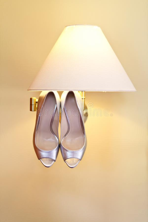 Silvery wedding shoes hanging on the ceiling of a beige lamp, minimalistic wedding concept, place for text. Silvery wedding shoes hanging on the ceiling of the stock image