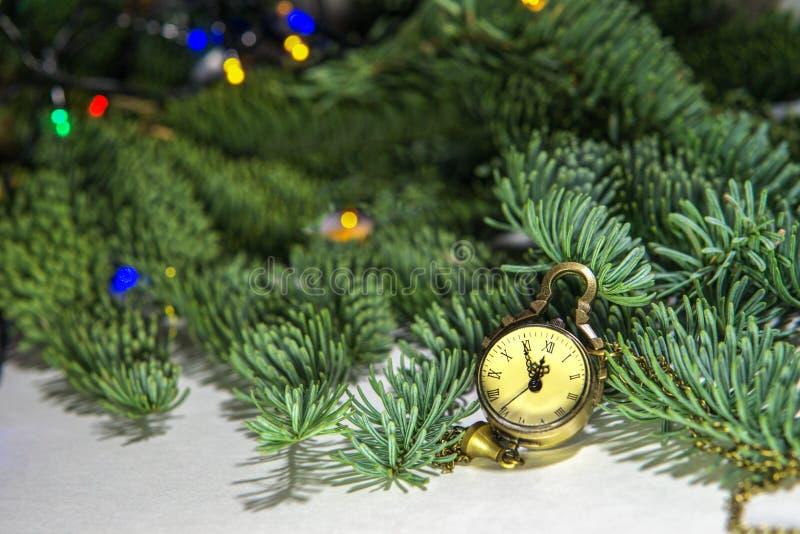 Silvesterabend, die Uhr - das Medaillon zeigt 23 55 Bald eine neue Zeit auf dem Hintergrund eines grünen Weihnachtsbaums lizenzfreie stockfotografie